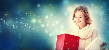 christmas present: Happy young woman opening a Christmas present box