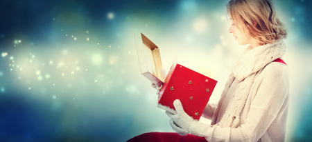 christmas present box: Young woman opening a Christmas present box