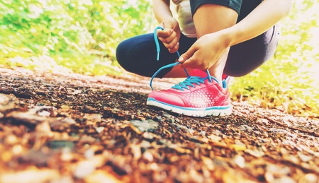 lacing sneakers: Female runner lacing her sneakers on a forest trail