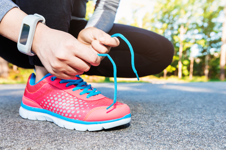 girl shoes: Female jogger ties her running shoes in preparation for a jog