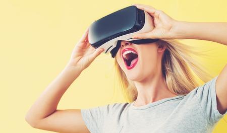 Gelukkige jonge vrouw met behulp van een virtual reality headset Stockfoto - 63993636