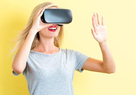 mujer joven feliz que usa un casco de realidad virtual