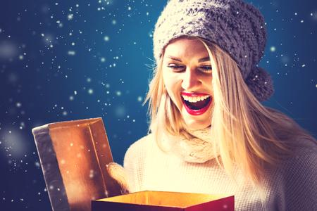 Glückliche junge Frau zur Eröffnung einer Weihnachtsgeschenk Box