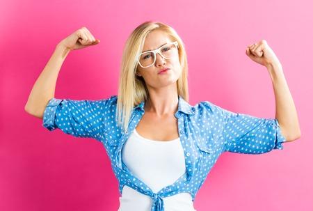 Leistungsstarke junge blonde Frau auf einem rosa Hintergrund
