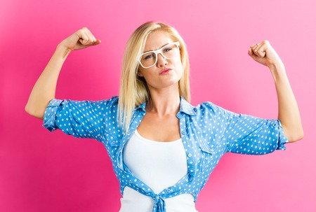 Powerful young blonde woman on a pink background Фото со стока - 63993733