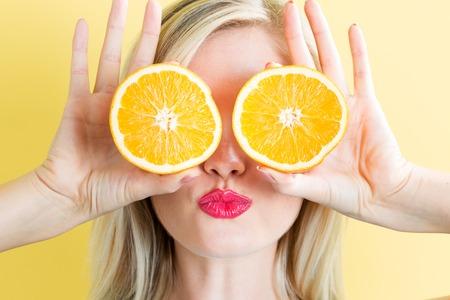Feliz joven mujer con naranjas sobre un fondo amarillo Foto de archivo