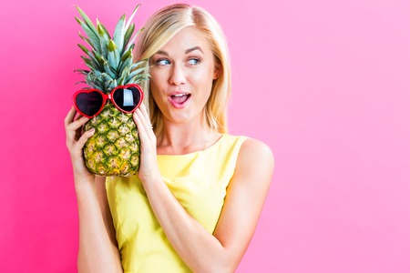 Happy young woman holding a pineapple on a pink background Zdjęcie Seryjne