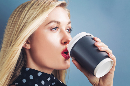 blonde females: Young blonde woman drinking coffee on a gray background Stock Photo