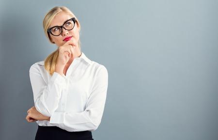 灰色の背景に思慮深いポーズの若い女性実業家