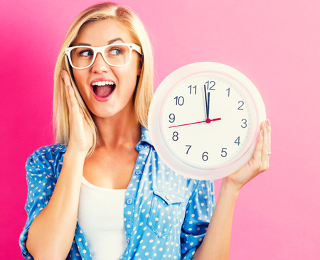 12 oclock: Young woman holding a clock showing nearly 12 Stock Photo