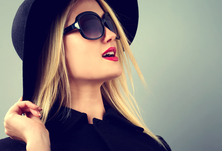 beautiful model: Beautiful young blonde woman in a black coat, hat and sunglasses
