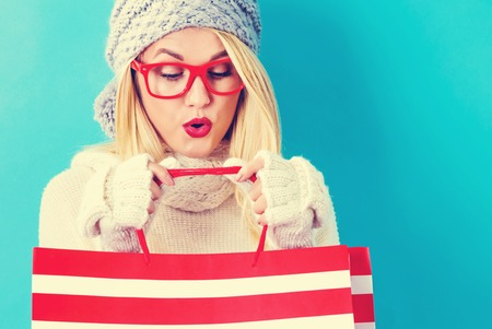 winter fashion: Happy young woman holding shopping bags on a blue background Stock Photo