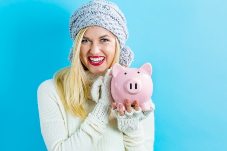 piggy: Young woman with a piggy bank on a blue background
