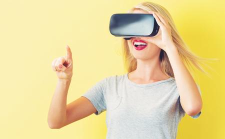 Mujer joven feliz que usa un casco de realidad virtual Foto de archivo - 63993886