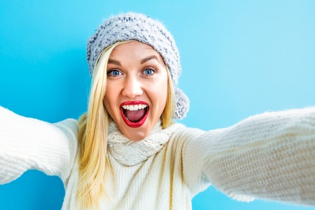 青色の背景に、selfie を取る若い女性