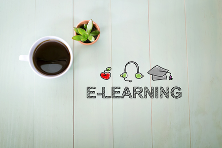 E-Learning concept with a cup of coffee on a pastel green wooden table