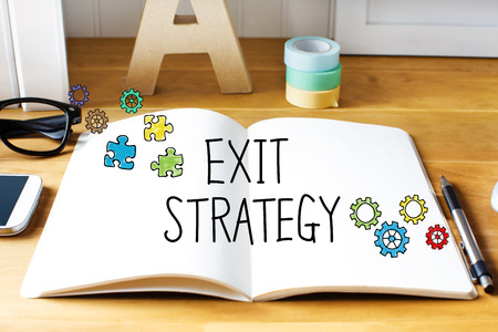 downsizing: Exit Strategy concept with notebook on wooden desk Stock Photo