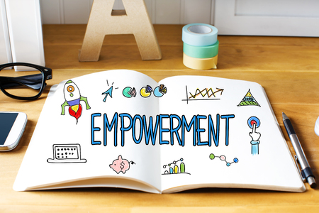 empowerment: Empowerment concept with notebook on wooden desk Stock Photo