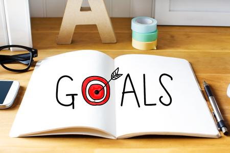 metas: Objetivos de concepto con el bloc de notas en el escritorio de madera