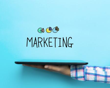 파란색 배경에 타블렛으로 마케팅 개념