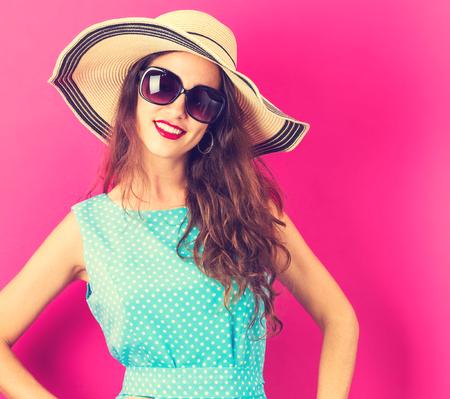 분홍색 배경에 모자와 선글라스를 착용 하 고 행복 한 젊은 여자