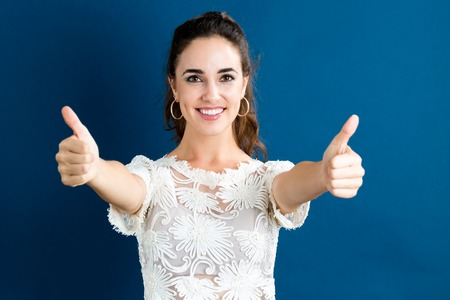 smiling face: Happy young woman giving thumbs on a dark blue background Stock Photo