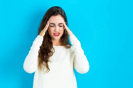 cabeza de mujer: Young woman feeling stressed on a blue background Foto de archivo