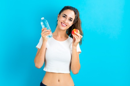 Happy young woman holding an apple and a water bottle Stock Photo - 64984509