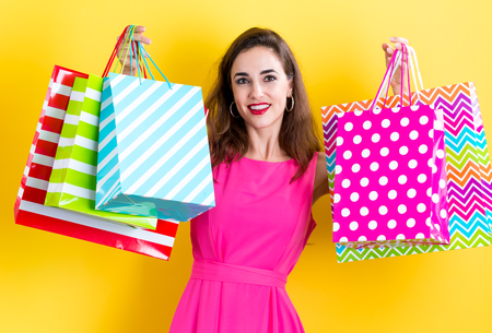 happy shopping: Happy young woman holding many shopping bags on a yellow background