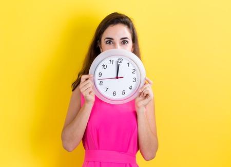 ほぼ 12 を示す時計を保持している女性
