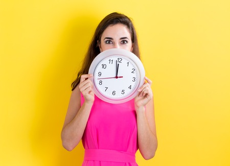 Woman holding a clock showing nearly 12