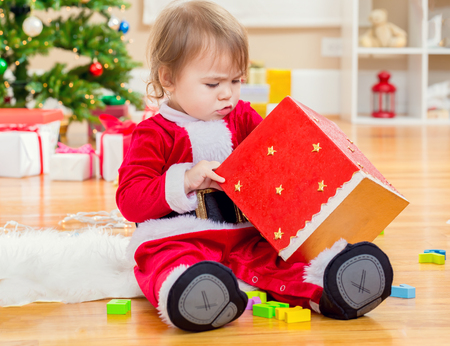 baby open present: Little toddler girl opening a big present box under by her Christmas tree Stock Photo
