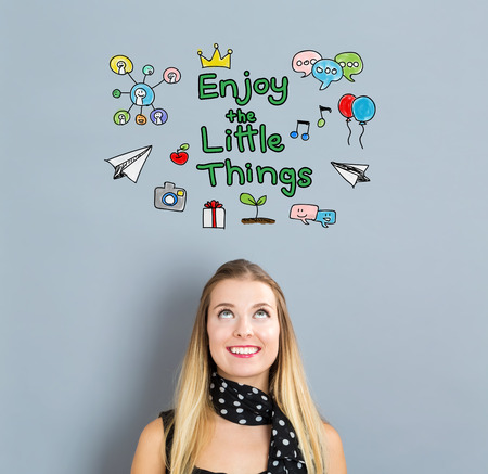 small business woman: Enjoy The Little Things concept with happy young woman on a gray background