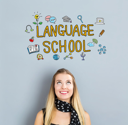 Language School concept with happy young woman on a gray background