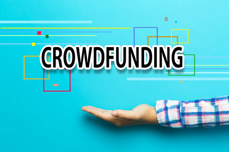 Crowdfunding concept with hand on blue background Stock Photo