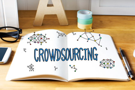 crowd source: Crowdsourcing concept with notebook on wooden desk Stock Photo