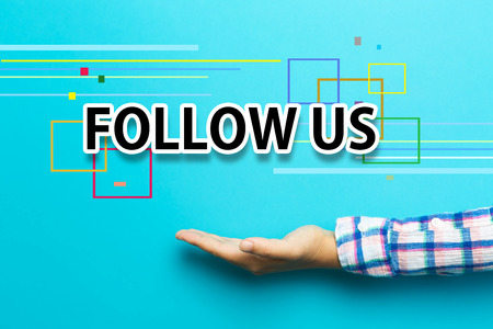 Follow Us concept with hand on blue background