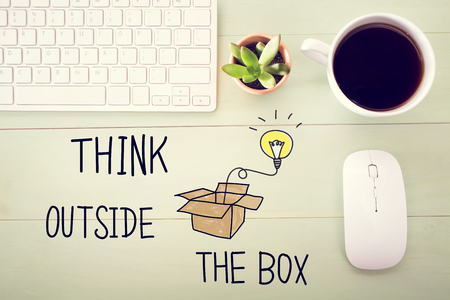 outside the box: Think Outside The Box concept with workstation on a light green wooden desk