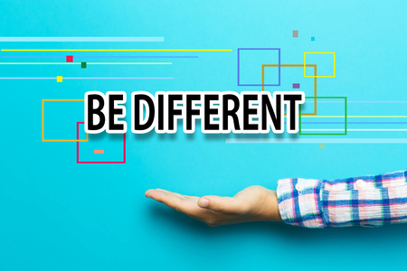 be: Be Different concept with hand on blue background
