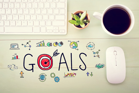 Goals concept with workstation on a light green wooden desk Stock Photo