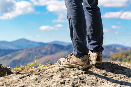 高い山の上の崖の端で男