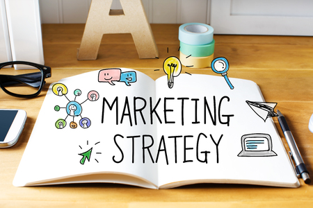 Marketing Strategy: Marketing Strategy concept with notebook on wooden desk