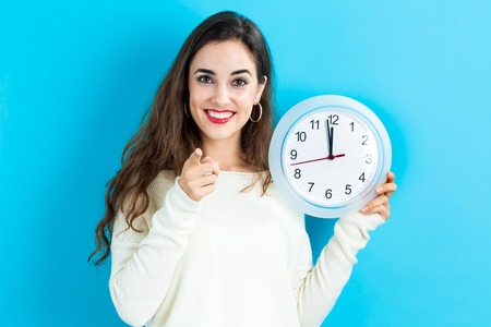 Young woman holding a clock showing nearly 12 Banco de Imagens - 64985039