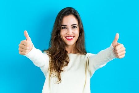 Gelukkige jonge vrouw geven thumbs up op een blauwe achtergrond Stockfoto