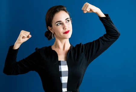 Krachtige jonge vrouw op een donkerblauwe achtergrond Stockfoto