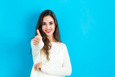 Glückliche junge Frau, die einen Daumen nach oben auf einem blauen Hintergrund zu geben Standard-Bild