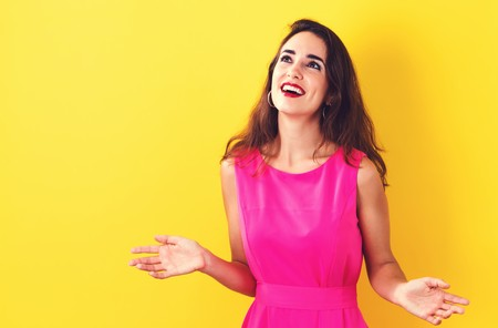 Happy young woman on a yellow background Stock Photo