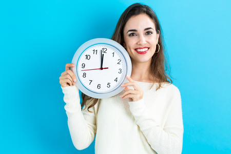 nearly: Young woman holding a clock showing nearly 12 Stock Photo