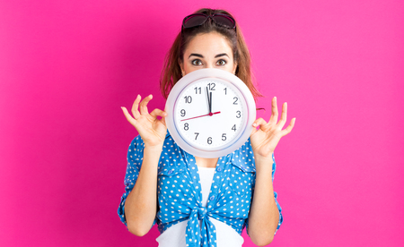 Young woman holding a clock showing nearly 12 Stockfoto