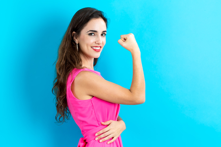 strong: Powerful young woman on blue background Stock Photo